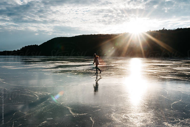 Young woman skating on frozen lake by Léa Jones for Stocksy United