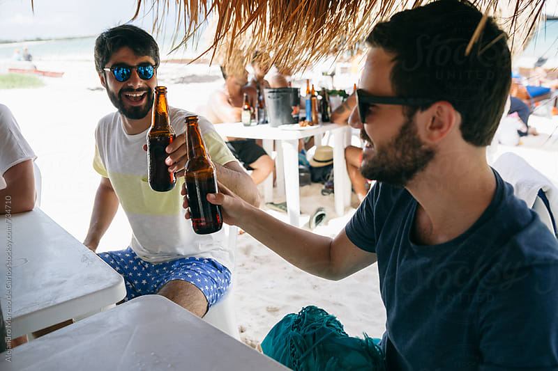Two friends toasting their bottle of beers on a beach bar by Alejandro Moreno de Carlos for Stocksy United