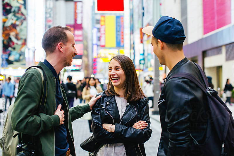 Happy tourist friends talking in Tokyo street. by BONNINSTUDIO for Stocksy United