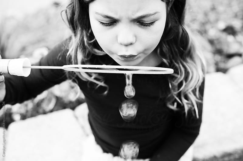 Black and white photo of a little girl blowing bubbles by Carolyn Lagattuta for Stocksy United