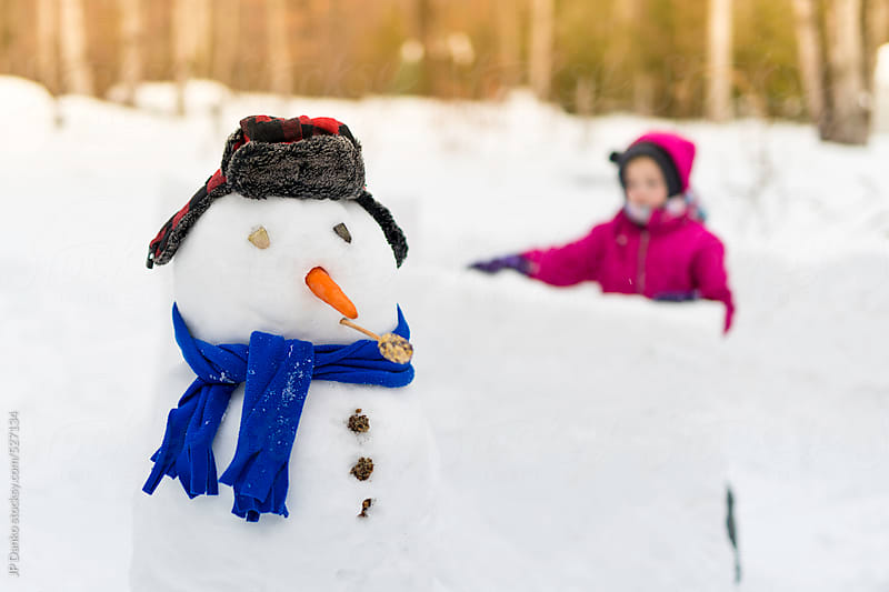 Girl Building a Snowfort with a Snowman in Winter by JP Danko for Stocksy United