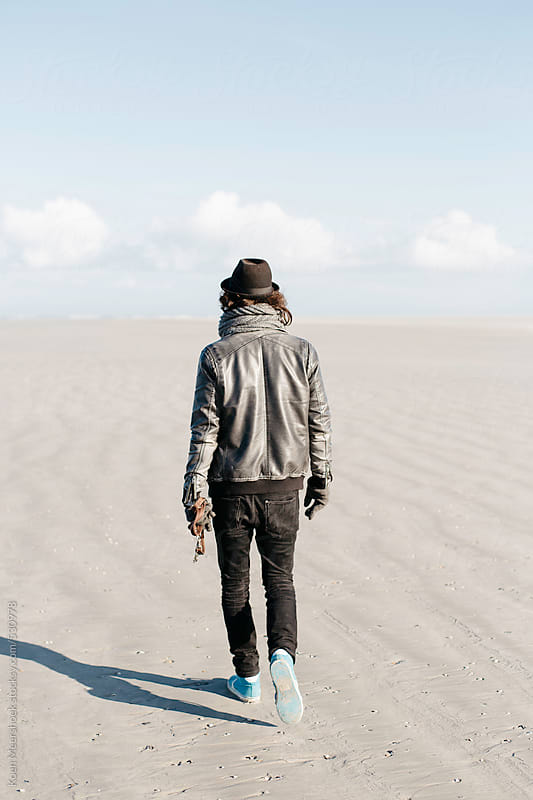 Hip young man walking alone on the beach. by Koen Meershoek for Stocksy United