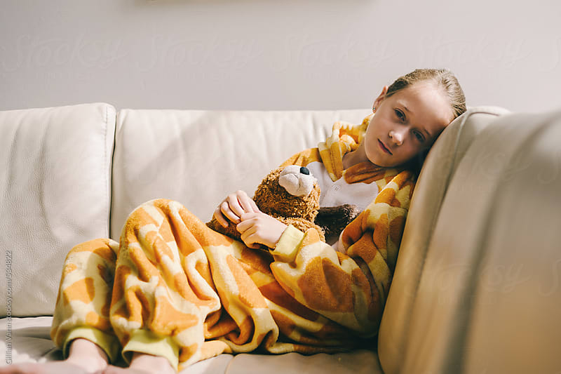 girl in onesie on the couch with her favourite teddy, quiet, sleepy by Gillian Vann for Stocksy United