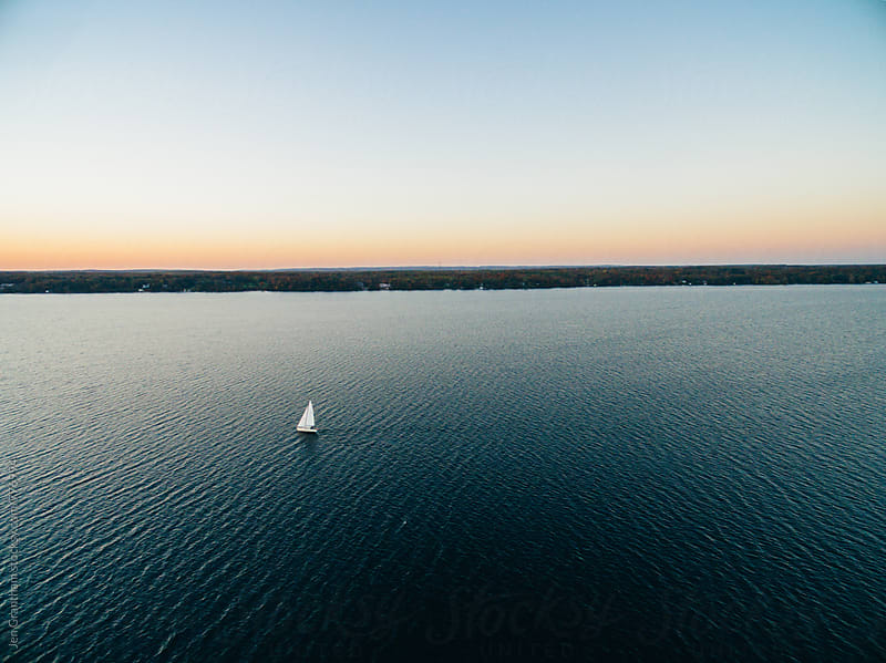 Aerial drone image of a sailboat sailing into sunset by Jen Grantham for Stocksy United