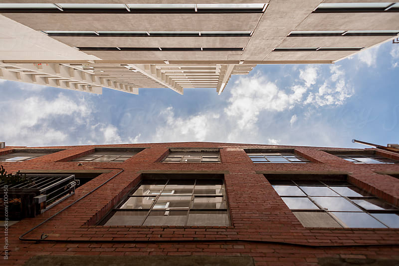 Looking up between old and new building facades by Ben Ryan for Stocksy United