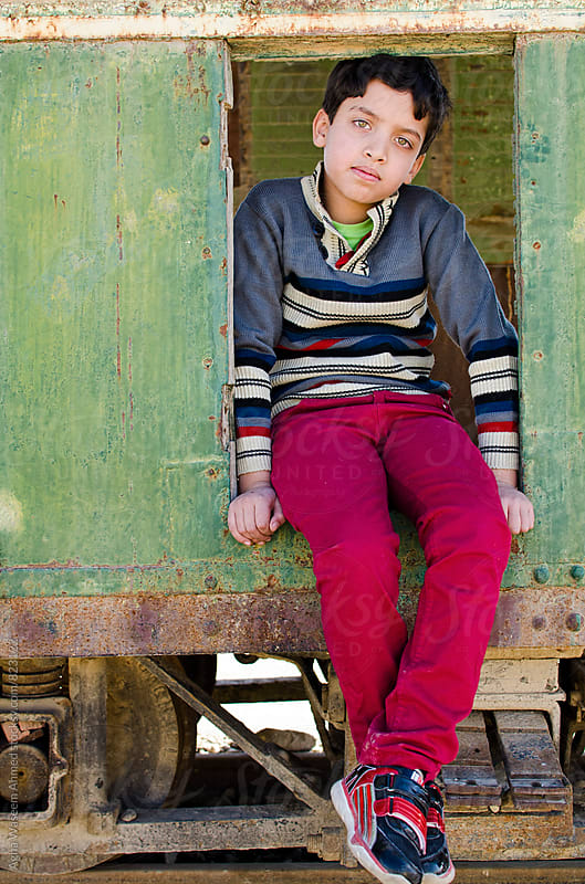 An adolescent boy sitting on the floor of a stationary railroad coach ! by Agha Waseem Ahmed for Stocksy United
