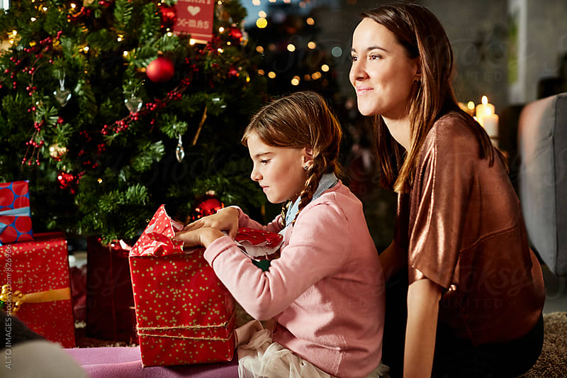 Mother With Daughter Opening Christmas Gift At Home by ALTO IMAGES for Stocksy United