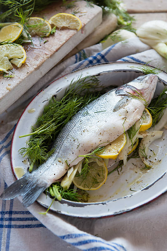 Fish prepared with lemons and  aromatic herbs on an old tray to put in the oven by Marta Muñoz-Calero Calderon for Stocksy United