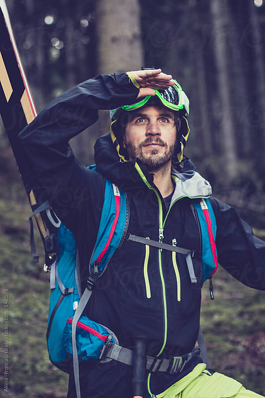 Freerider walking through the forest with his whole skiing equipment by Leander Nardin for Stocksy United