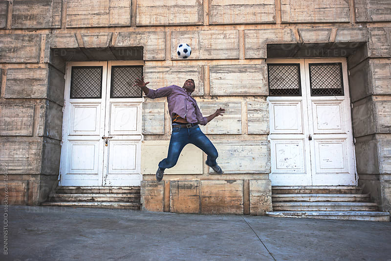 Black man jumping with soccer ball on the street in front two big white doors. by BONNINSTUDIO for Stocksy United