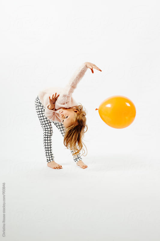 Young female child playing with an orange balloon by Christina Rouse for Stocksy United