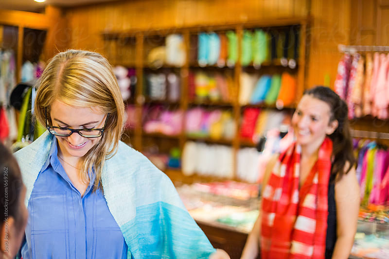 Two friends in a Thai silk store by Jovo Jovanovic for Stocksy United