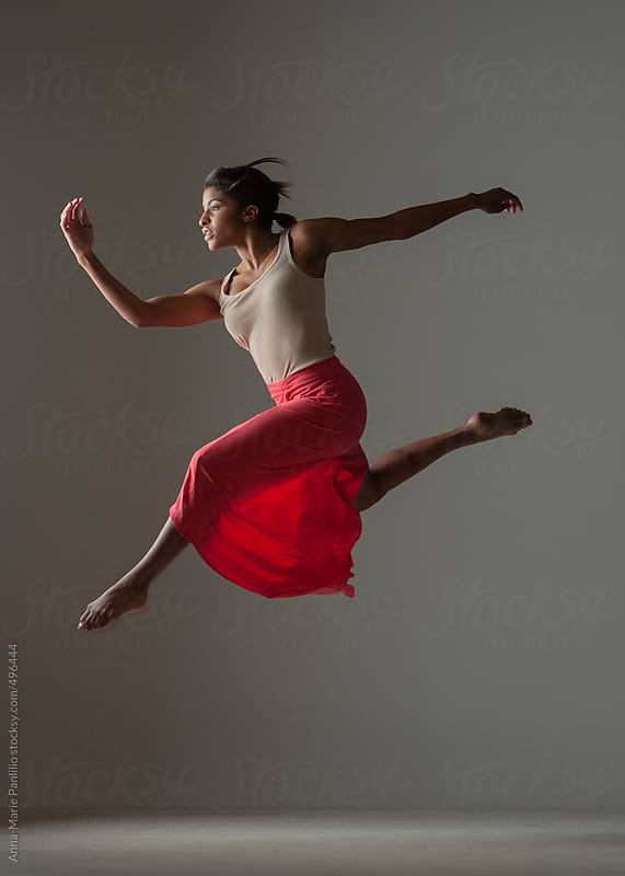 Black woman in red skirt dancing by Anna-Marie Panlilio for Stocksy United