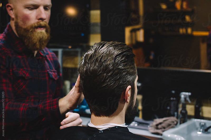 Barber styles young males hair by Jesse Morrow for Stocksy United