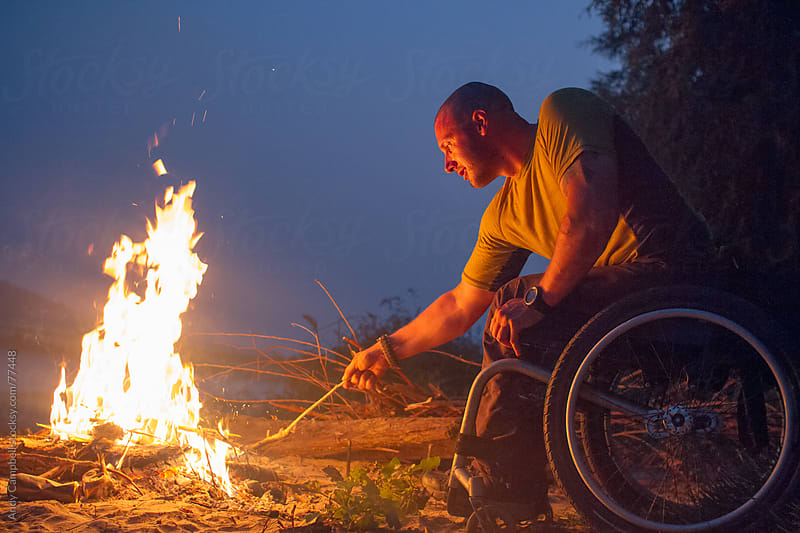 A paraplegic man sitting in a wheelchair stokes a campfire on a beach at night. by Andy Campbell for Stocksy United