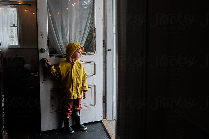 little kid stating in the door with raincoat on by Léa Jones for Stocksy United