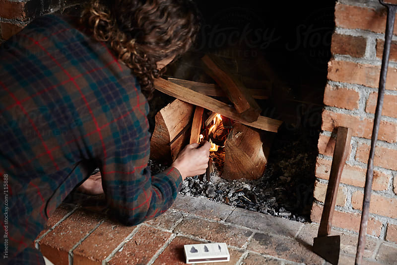 Man building a fire in his fireplace  by Trinette Reed for Stocksy United