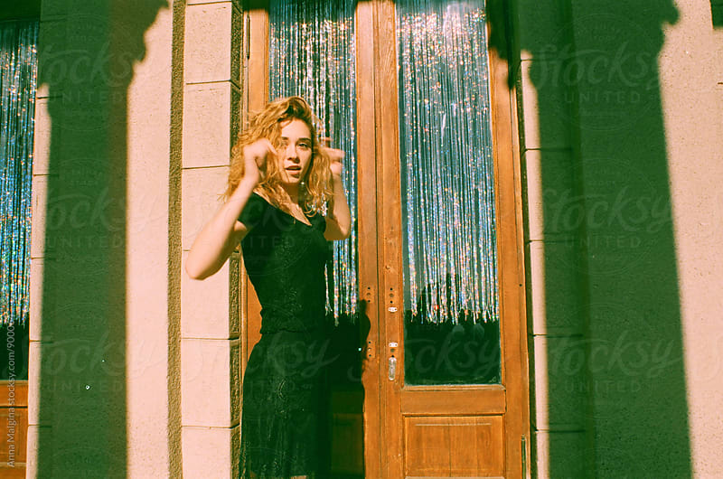 A film portrait of young beautiful redhead woman dancing in front of a door by Anna Malgina for Stocksy United