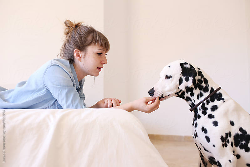 Blonde girl playing with a dalmatian dog by Lucas Ottone for Stocksy United