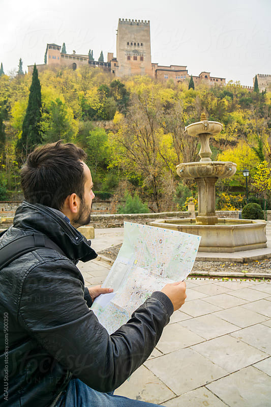 Tourist looking a map next to Alhambra of Granada by ACALU Studio for Stocksy United