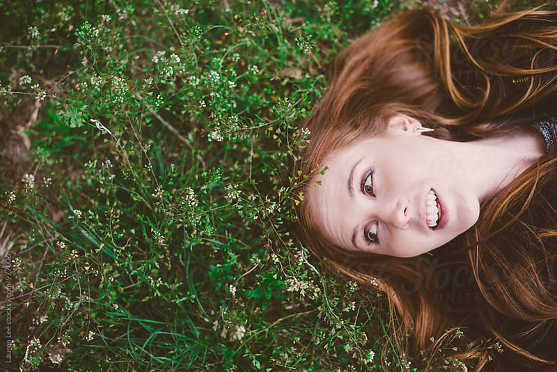 Young redhead woman lying in grass by Lauren Naefe for Stocksy United