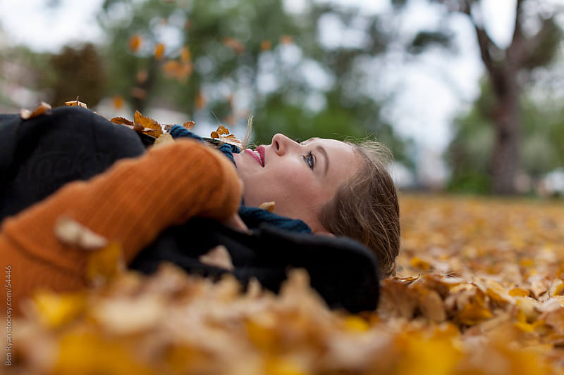 Stylish young woman lying on her back in autumn leaves by Ben Ryan for Stocksy United