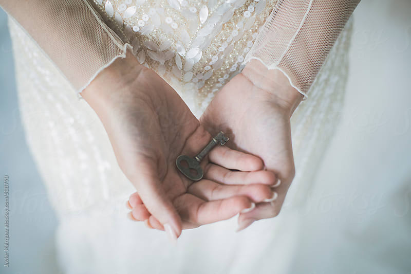 Bride on her wedding day with old key in hands by Javier Márquez for Stocksy United