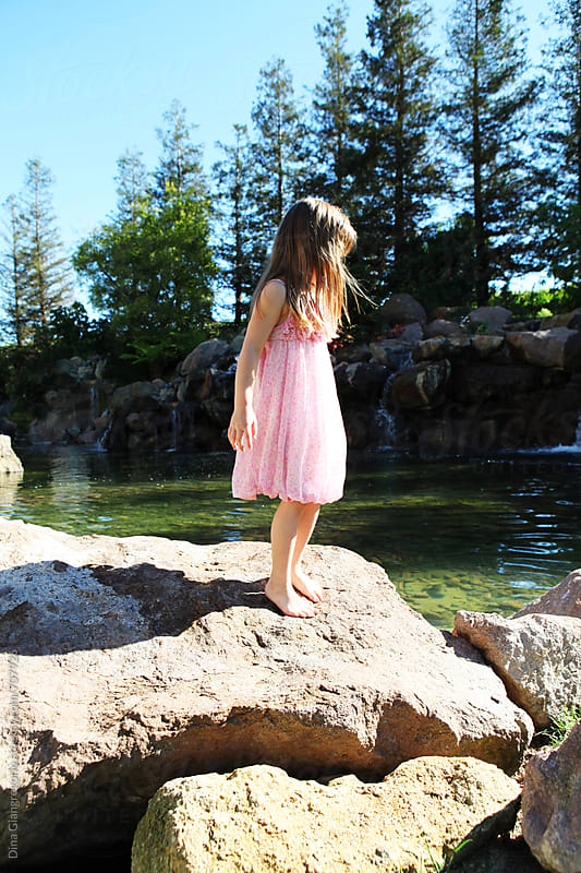 Girl In Pink Dress Standing on Rocks Near Tall Trees by Dina Giangregorio for Stocksy United