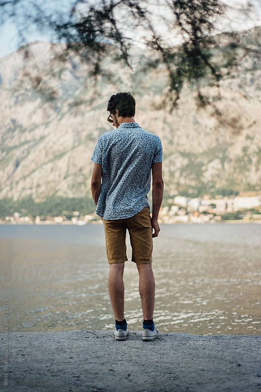 Fashionable man standing by the sea by Boris Jovanovic for Stocksy United
