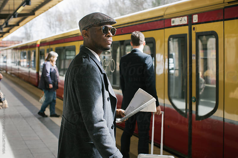 Stylish Black Businessman Standing in Train Station as Train is Arriving by Julien L. Balmer for Stocksy United