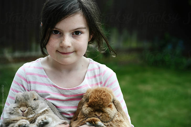 Smiling girl holds two lop-eared rabbits by Kirstin Mckee for Stocksy United