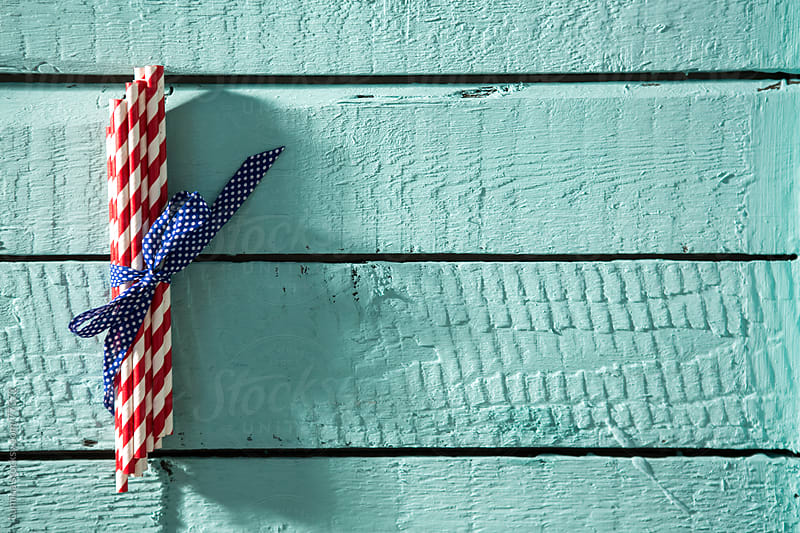Bunch of Striped Straws on a Blue Wooden Board by Lumina for Stocksy United