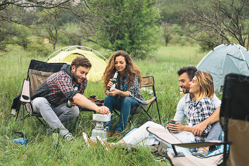 Young people camping and chatting outdoors by Aleksandar Novoselski for Stocksy United