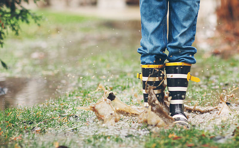 child splashing in a mud puddle by Kelly Knox for Stocksy United