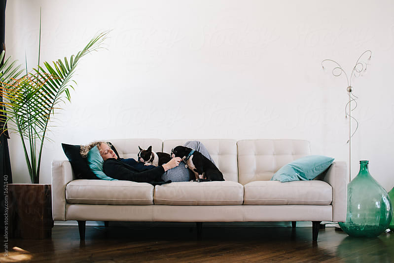 a woman laying on a couch with her two dogs by Sarah Lalone for Stocksy United