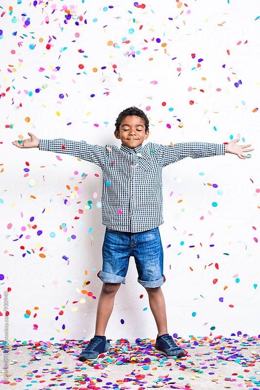 Little boy playing with confetti falls from above. by BONNINSTUDIO for Stocksy United