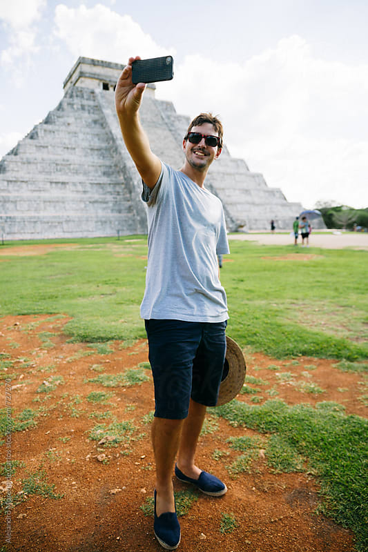 Young tourist man taking a selfie with his phone in Kukulkan pyramid in Chichen Itza, Mexico by Alejandro Moreno de Carlos for Stocksy United