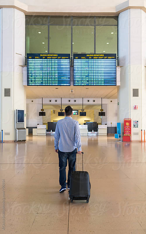 Man Walking with the Suitcase at the Airport by ACALU Studio for Stocksy United