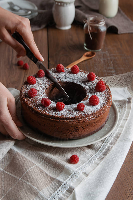 Woman cutting a piece of a chocolate cake with raspberries by Nataša Mandić for Stocksy United