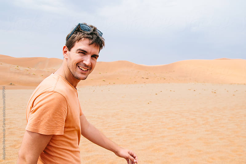 Side portrait of a young happy adventurous man walking in the middle of the desert by Alejandro Moreno de Carlos for Stocksy United
