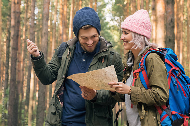 Happy couple with map in forest