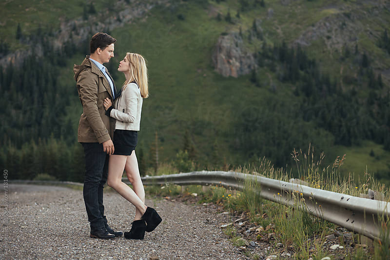 A couple standing on a gravel mountain road looking into each others eyes by Ania Boniecka for Stocksy United