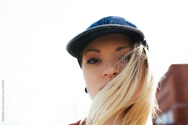 Closeup of Blond Woman with Wind Blowing Her Hair by Gabrielle Lutze for Stocksy United