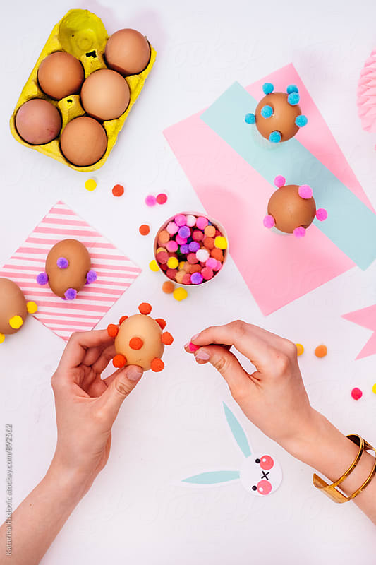 Woman Decorating Easter Eggs With Colourful Pompons by Katarina Radovic for Stocksy United