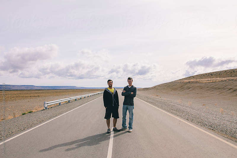 Two male friends standing on the middle of a road - highway by Alejandro Moreno de Carlos for Stocksy United