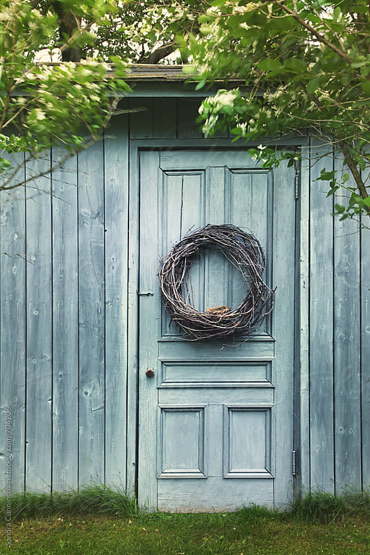 Old blue barn door with wreath by Sandra Cunningham for Stocksy United