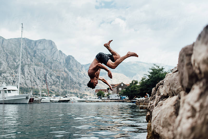 Man jumping into the water by Boris Jovanovic for Stocksy United