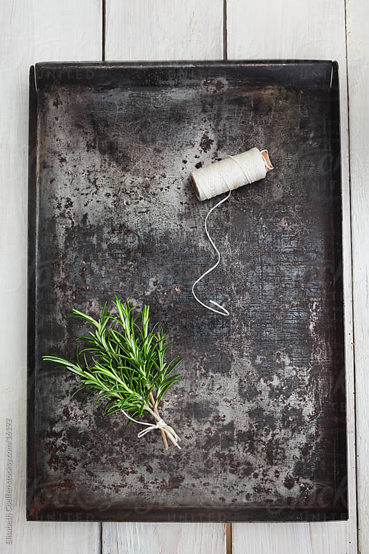 Bunch of rosemary with a spool of kitchen string on old rusty baking tray by Elisabeth Coelfen for Stocksy United