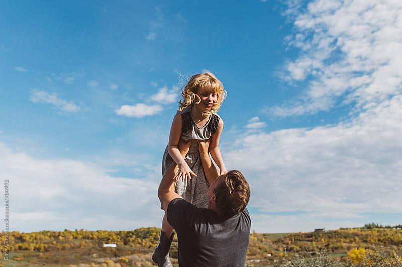 Father playfully throwing daughter in sky by Carey Shaw for Stocksy United