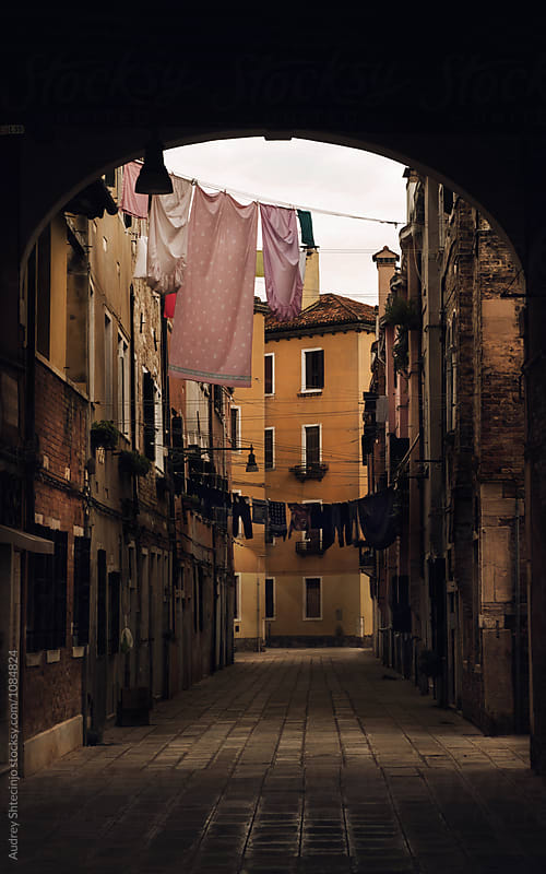 Narrow alley with clothes hanging on line between locals residences during evening hours.Venice/Italy by Marko Milanovic for Stocksy United